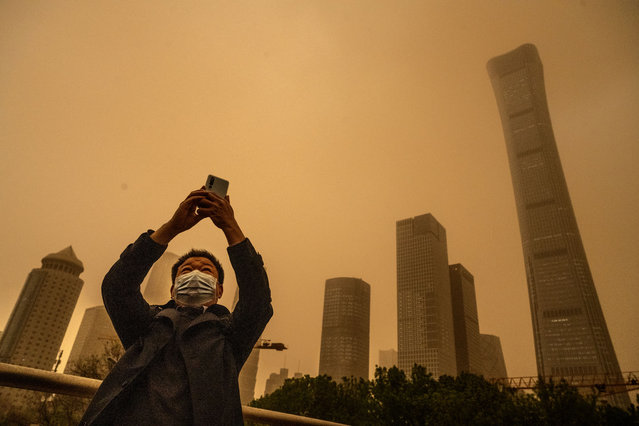 A man wears a protective mask as he takes photos during a seasonal sandstorm on April 15, 2021 in Beijing, China. China's capital and the northern part of the country typically experience sandstorms that originate in the Gobi desert, but scientists believe that climate change and desertification also plays a role in their frequency and intensity. (Photo by Kevin Frayer/Getty Images)