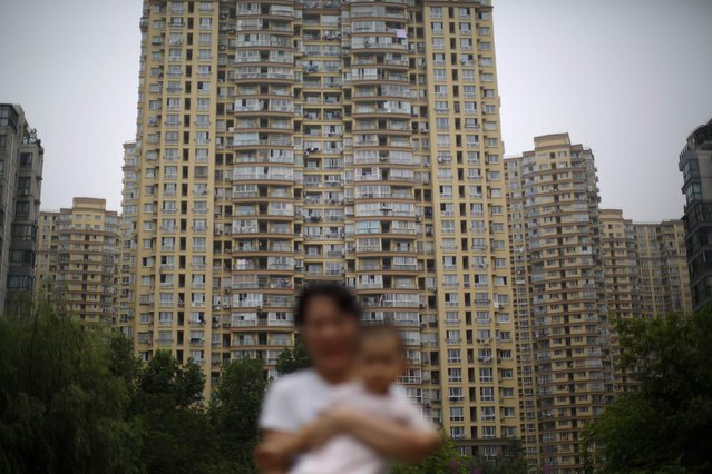 A woman holds her son in a playground in a residential area in Shanghai in this July 26, 2014 file photo. China's new home prices may have bottomed and even started to rebound in January after eight months of decline, industry surveys showed, fuelling hopes that official data due on February 17, 2015 will confirm a recovery in the massive property market. (Photo by Carlos Barria/Reuters)