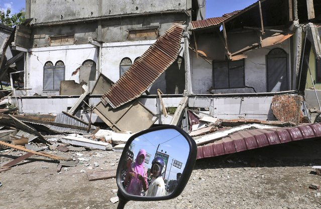 Women are reflected in a motorbike's mirror as they access the damaged building after an earthquake in Pidie Jaya, Aceh province, Indonesia, Wednesday, December 7, 2016. (Photo by Heri Juanda/AP Photo)