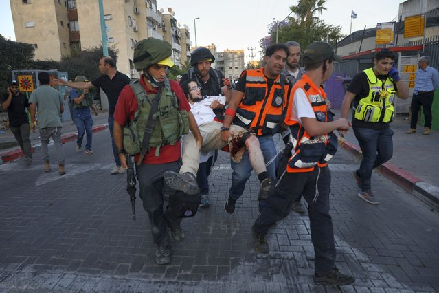 Israeli security forces and paramedics carry a wounded Jewish man after he was shot during violent unrest in Lod, Israel, Thursday, May 13, 2021. The man was shot, allegedly by an Arab man, during violent clashes between Jews and Arabs in the central city of Lod, Israeli media reported. (Photo by Ofer Vaknin/AP Photo)