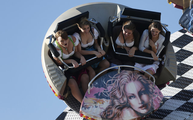 """Young women enjoy a fairground ride at the 180th Bavarian """"Oktoberfest"""" beer festival in Munich, southern Germany, Wednesday, October 2, 2013. One of the world's largest beer festival to be held from Sept. 21 to October 6, 2013 will attract more than six million guests from around the world. (Photo by Matthias Schrader/AP Photo)"""