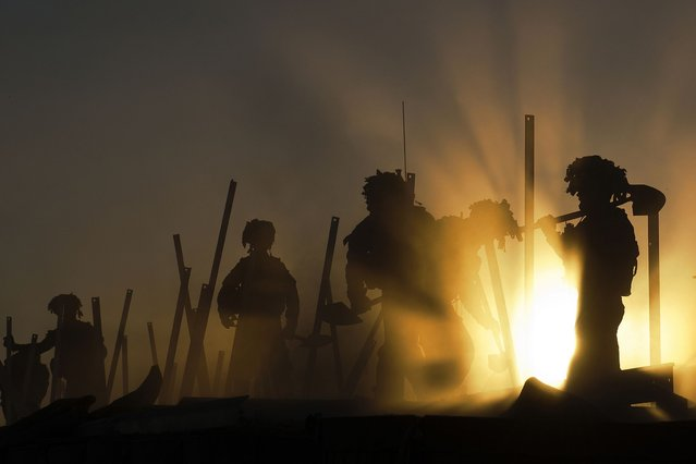 """Jamie's photograph, """"Sunset Soldiers"""", shows sappers demolishing a former British Base. (Photo by Jamie Peters/PA Wire)"""