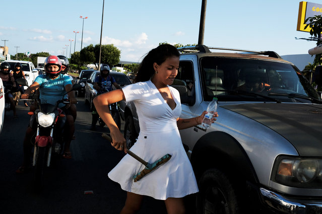 Anyi Gomez, 19, a pregnant Venezuelan woman from Monagas state, is pictured between cars as she washes car windows at a traffic light in Boa Vista, Roraima state, Brazil on August 24, 2018. (Photo by Nacho Doce/Reuters)