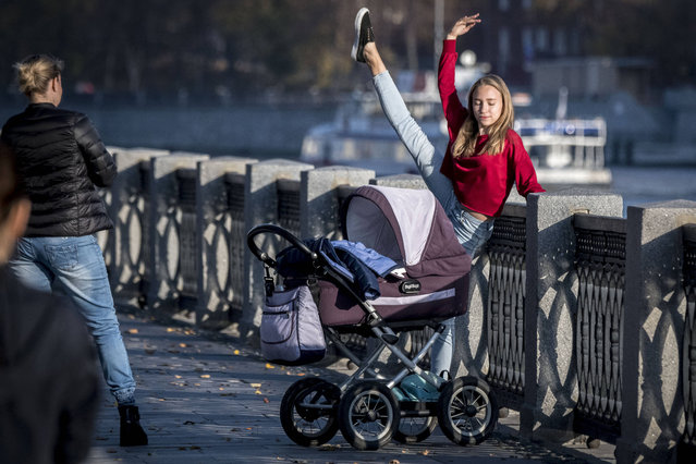 A girl stretches next to a pram on the embankment of the Moskva river in Moscow on October 18, 2018. The European part of Russia enjoys an unusually warm weather for the season with temperatures reaching up to 22 degrees centigrade. (Photo by Mladen Antonov/AFP Photo)