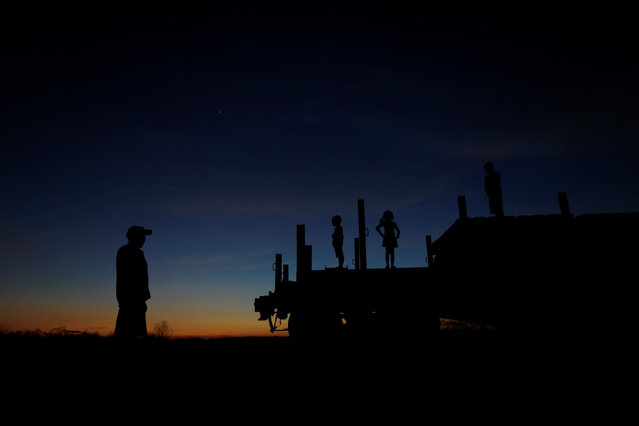 Raimundo da Silva stands nearby as his sons Daniel da Silva, Ariana da Silva and Raniel da Silva play on top of a train wagon near the city of Salgueiro, Pernambuco state, northeastern Brazil, October 26, 2016. (Photo by Ueslei Marcelino/Reuters)