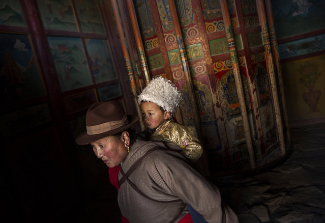ATibetan Buddhist woman carries a child passed a large prayer wheel during Monlam or the Great Prayer rituals on March 3, 2015 at the Labrang Monastery, Xiahe County, Amdo, Tibetan Autonomous Prefecture, Gansu Province, China. (Photo by Kevin Frayer/Getty Images)