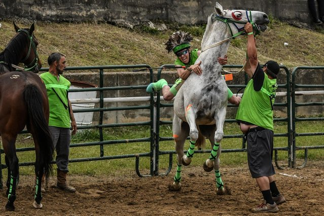 A rider from the Arrow Lakes team jumps onto a bareback horse while Native Americans from all over the United States participate in an Indian relay race over Memorial Day weekend at the Osage County Fairgrounds in Pawhuska, Oklahoma, U.S. May 31, 2021. (Photo by Stephanie Keith/Reuters)