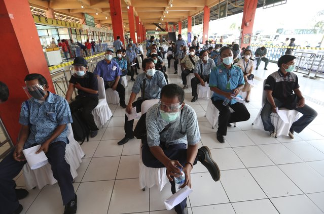 Transportation workers wear face masks and shields to help curb the spread of the coronavirus while waiting for the AstraZeneca vaccine during a mass vaccination campaign for public transport workers at the Kampung Rambutan Bus Terminal in Jakarta, Indonesia, Thursday, June 10, 2021. (Photo by Achmad Ibrahim/AP Photo)