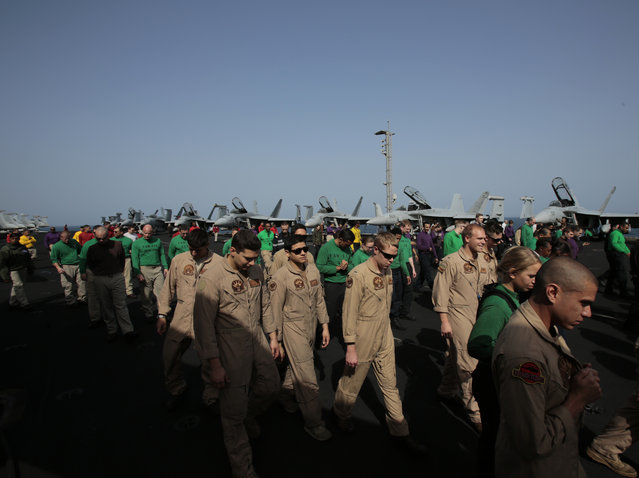 U.S. sailors and pilots walk on the flight deck, checking for any debris, aboard the USS Carl Vinson aircraft carrier in the Persian Gulf, Thursday, March 19, 2015. (Photo by Hasan Jamali/AP Photo)