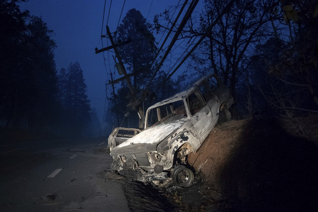 A scorched vehicle rests on a roadside as the Camp Fire tears through Paradise, Calif., on Thursday, November 8, 2018. Tens of thousands of people fled a fast-moving wildfire Thursday in Northern California, some clutching babies and pets as they abandoned vehicles and struck out on foot ahead of the flames that forced the evacuation of an entire town and destroyed hundreds of structures. (Photo by Noah Berger/AP Photo)