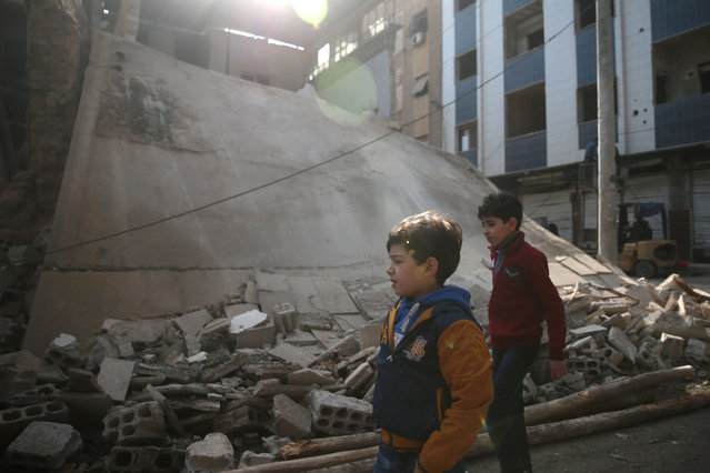 Boys walk near a damaged building in the rebel held besieged city of Douma, in the eastern Damascus suburb of Ghouta, Syria December 30, 2016. (Photo by Bassam Khabieh/Reuters)