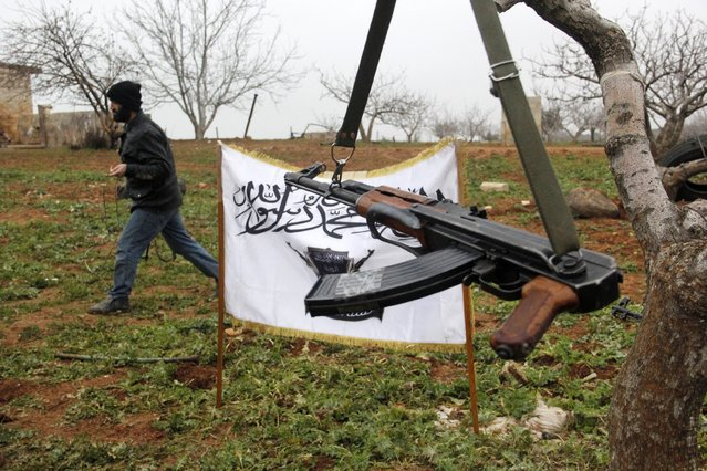 A Free Syrian Army fighter walks past a flag of al-Furqan brigade as a rifle hangs from a branch in the orchards of Kafar Zita in Hama countryside January 22, 2015. (Photo by Mohamad Bayoush/Reuters)