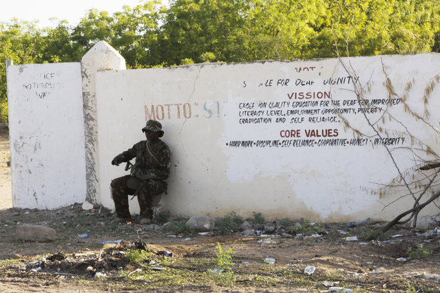 A Kenya Defence Forces soldier secures the area around the Garissa University college, in Garissa, Kenya, Thursday, April 2, 2015. Al-Shabab gunmen attacked Garissa University College in northeast Kenya early Thursday, targeting Christians and killing over 100 people and wounding others, according to Kenya's national disaster operations center and the interior minister. (Photo by Khalil Senosi/AP Photo)