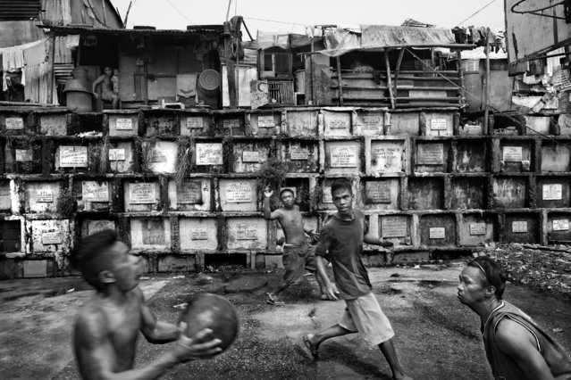 """""""Playing Ball Among the Dead"""". Boys playing basketball among the tombs of the Navotas Cementery. Photo location: Navotas City, Metro Manila, Philippines. (Photo and caption by Larry Louie/National Geographic Photo Contest)"""