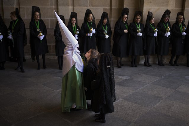 """Children play as penitents of the """"Virgen de la Esperanza"""" brotherhood march as they  take part in a Holy Week procession in Zamora, Spain, Thursday, April 2, 2015. Hundreds of processions take place throughout Spain during the Easter Holy Week. (Photo by Andres Kudacki/AP Photo)"""