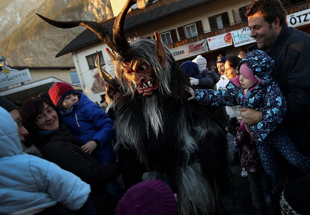 A member of the Haiminger Krampusgruppe dressed as the Krampus creature lets himself be touched by onlookers prior to the annual Krampus night in Tyrol in Haiming. (Photo by Sean Gallup)
