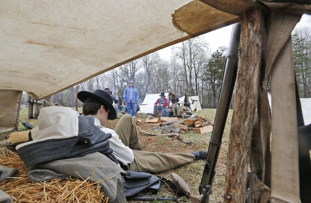 Confederate re-enactors take a break in their camp as part of  the commemoration of the 150th anniversary of the surrender of the Army of Northern Virginia at Appomattox Court House in Appomattox, Va., Thursday, April 9, 2015. (Photo by Steve Helber/AP Photo)