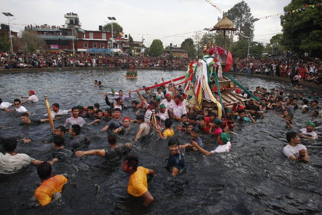 Nepalese devotees carry a chariot of Hindu goddess Tudaldevi into a pond during Gahana Khoje Jatra or Searching for lost Jewelry festival in Kathmandu, Nepal, Sunday, April 5, 2015. According to Hindu Mythology goddess Tudaldevi lost her jewelry while she was taking bath in the pond so every year devotees gather and carry her chariot to help her to find her lost jewelry. (Photo by Niranjan Shrestha/AP Photo)