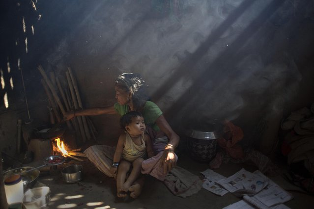 In this Tuesday, March 31, 2015 photo, an elderly Indian woman cooks using firewood at her home at Gobhali village on the outskirts of Gauhati, India. Every evening, hundreds of millions of Indian women hover over crude stoves making dinner for their families. They feed the flames with polluting fuels like kerosene or cow dung, and breathe the acrid smoke wafting from the fires. (Photo by Anupam Nath/AP Photo)