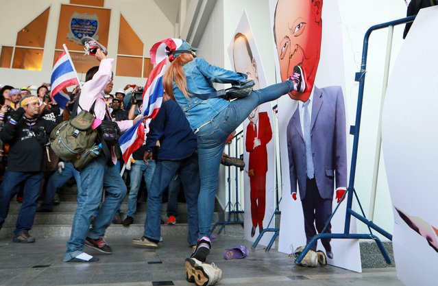Anti-government protesters kick at drawings of Tharit Pengdit, chief of the Department of Special Investigation (DSI), after storming into his office during a rally in Bangkok, Thailand, Monday, December 23, 2013. About 5,000 protesters stormed into the DSI office building when the DSI charged the protest leaders on illegal demonstrations and frozen their bank accounts last week. (Photo by Wason Wanichakorn/AP Photo)