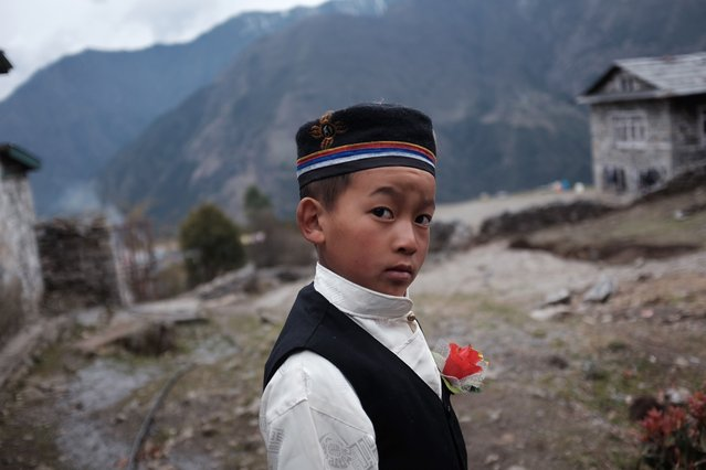 Rinji, 10, a young resident of the north eastern Nepalese town of Lukla wears a plastic flower on his lapel near his school on April 15, 2015.  Rinji wears a traditional Nepalese outfit of the Magar culture as he and classmates prepare a presentation for their parents in the coming days. Lukla is the gateway for most treks in the Khumbu region including Mount Everest. (Photo by Roberto Schmidt/AFP Photo)