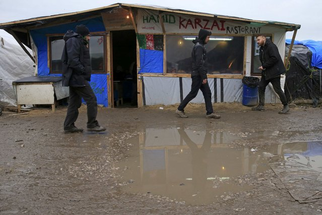 """Migrants walk past a makeshift Afghan restaurant called """"Hamid Karzai"""" in the southern part of a camp for migrants called the """"jungle"""", in Calais, northern France, February 23, 2016. (Photo by Pascal Rossignol/Reuters)"""