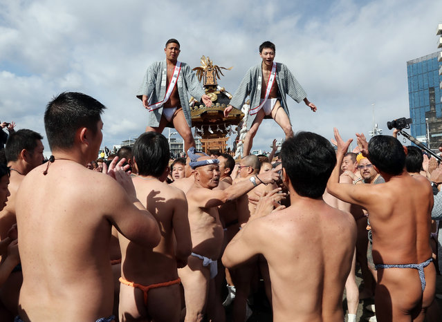 New adults stand on a portable shrine carried along the seashore during a purification ceremony at Katase-Enoshima beach on January 15, 2017 in Fujisawa, Japan. The annual festival with portable shrines celebrates the coming-of-age for young people. (Photo by Aflo/Barcroft Images)