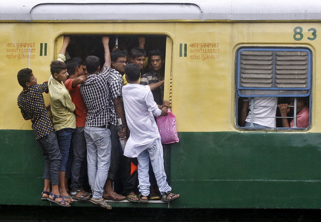 Commuters stand at an open doorway of a suburban train during the morning rush hour in Kolkata, India, July 31, 2015. (Photo by Rupak De Chowdhuri/Reuters)