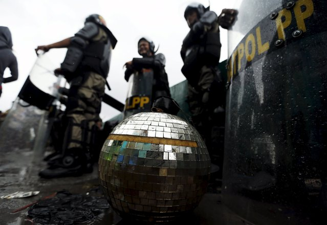 A disco ball is seen near civil service police unit members as buildings are demolished at Kalijodo red-light district in Jakarta, Indonesia, February 29, 2016. (Photo by Reuters/Beawiharta)
