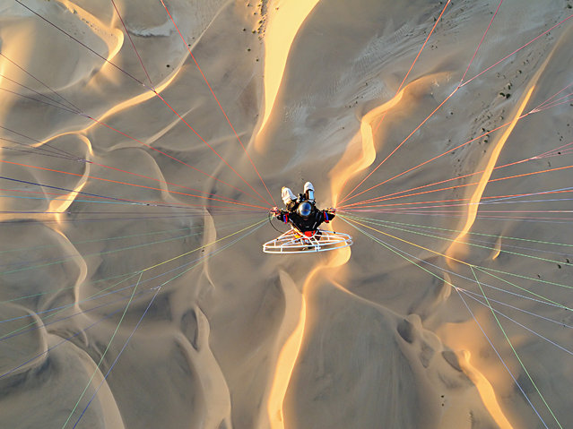 Theo Allofs flying with a powered paraglider over sand dunes near Walvis Bay, in October, 2014, in the Namib Desert, Namibia. (Photo by Theo Allofs/Barcroft Media)