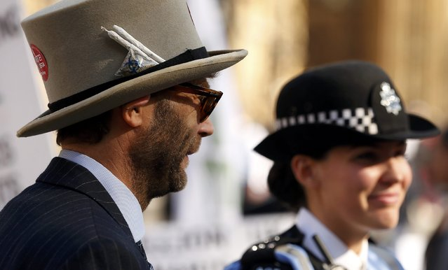 A man stands next to a police officer as he wears a hat with two cannabis joints tucked into the strap during a pro-cannabis rally beside the Houses of Parliament in London, April 20, 2015. (Photo by Cathal McNaughton/Reuters)