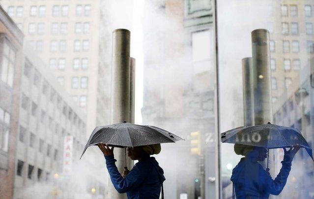 A woman shields herself with an umbrella during an afternoon rainstorm in Philadelphia, on Oktober 11, 2013. (Photo by Matt Rourke/Associated Press)