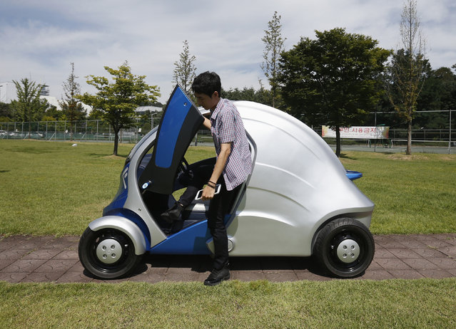 """A researcher gets out of """"Armadillo-T"""", a foldable electric vehicle, at the Korea Advanced Institute of Science and Technology in Daejeon, South Korea Wednesday, September 4, 2013. (Photo by Kim Hong-Ji/Reuters)"""