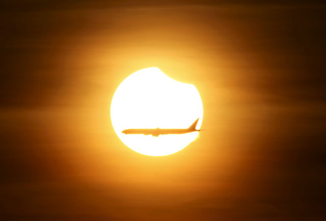 An aeroplane flies past the sun as it goes into a partial solar eclipse in Singapore March 9, 2016. (Photo by Edgar Su/Reuters)