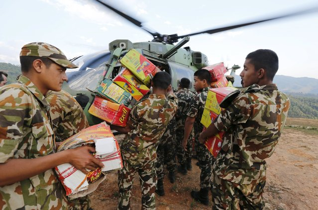 Nepalese soldiers load goods into an army helicopter in Gorkha, Nepal, to supply remote areas near the epi-centre of Saturday's earthquake with food and other needs, April 29, 2015. (Photo by Wolfgang Rattay/Reuters)
