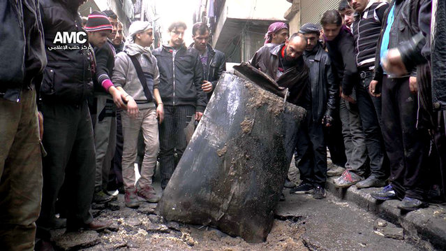 In this Sunday, January 19, 2014 file photo, provided by Aleppo Media Center (AMC), an anti-Bashar Assad activist group, which has been authenticated based on its contents and other AP reporting, Syrian citizens inspect an unexploded barrel of explosives which was dropped from a Syrian forces helicopter, on a street in Aleppo, Syria. (Photo by AP Photo/Aleppo Media Center)