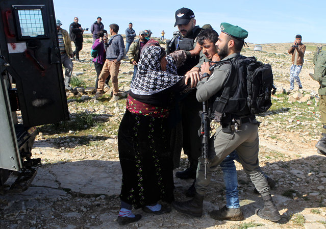 Palestinian women attempt to free a detained relative from being taken into an Israeli military vehicle during demolishing of housing in the village of Tuba near the West Bank city of Yatta, south of Hebron, 20 March 2019. The Israeli army demolished houses of Palestinians who do not have the Israeli needed permits to build housing or infrastructure in Area C of the occupied West Bank. (Photo by Abed Al Hashlamoun/EPA/EFE)