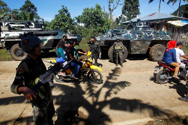 Motorists and commuters drive past soldiers at a checkpoint in Butig, Lanao del Sur in southern Philippines February 1, 2017. (Photo by Marconi B. Navales/Reuters)