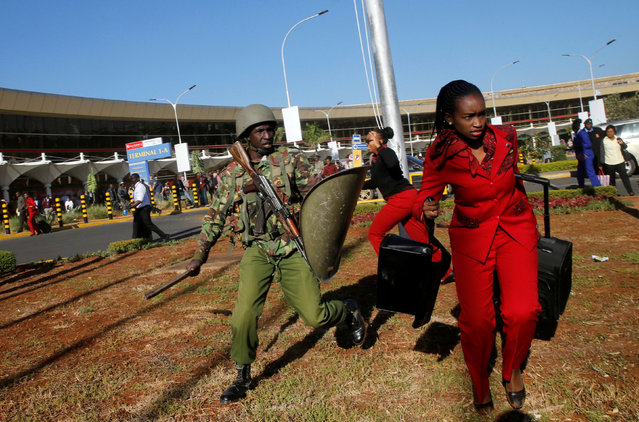 A Kenya Airways worker is dispersed by riot police at the Jomo Kenyatta International Airport during a labour dispute that grounded flights near Nairobi, Kenya on March 6, 2019. Hundreds of travellers were stranded at Nairobi's international airport as riot police were deployed and teargas fired to disperse striking workers. With flights grounded since midnight, passengers were advised not to come to the Jomo Kenyatta International Airport – East Africa's busiest according to the Kenya Airports Authority (KAA) – until further notice. (Photo by Thomas Mukoya/Reuters)