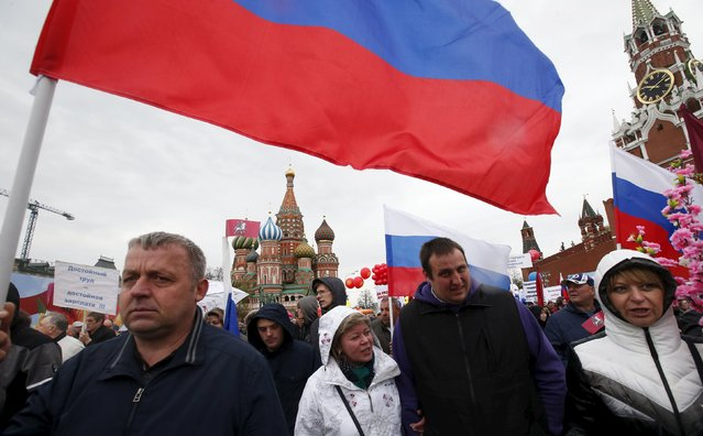 People walk with flags at Red Square during a May Day rally in Moscow May 1, 2015. (Photo by Maxim Zmeyev/Reuters)