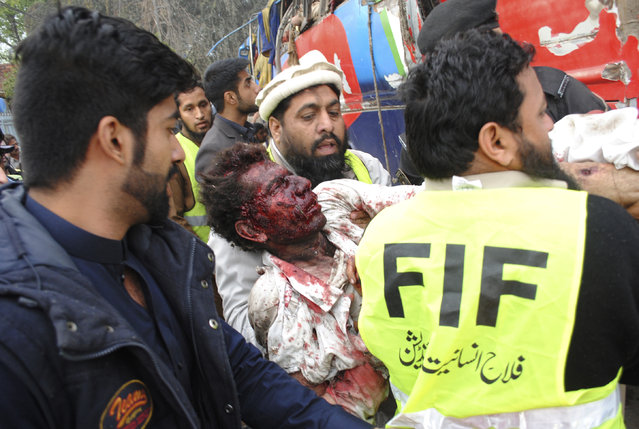 Pakistani volunteers carry an injured passenger following a bomb blast in Peshawar, Pakistan, Wednesday, March 16, 2016. (Photo by Mohammad Sajjad/AP Photo)