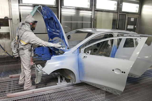 An employee works on the automobile assembly line of a Renault Clio IV at the Renault automobile factory in Flins, west of Paris, France, May 5, 2015. France's car sales rose 2.3 percent in April to reach 170,768 registrations with Renault's performance outpacing its peer Peugeot, the CCFA industry association said on Monday. (Photo by Benoit Tessier/Reuters)