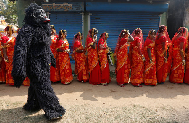 A performer dressed in a chimpanzee costume walks past brides as they arrive at a mass marriage ceremony in which, according to its organizers, 109 tribal, Muslim and Hindu couples from various villages across the state took their wedding vows, at Bahirkhand village, north of Kolkata,  February 5, 2017. (Photo by Rupak De Chowdhuri/Reuters)