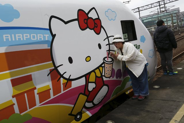 Fans pose next to Hello Kitty-themed Taroko Express train in Taipei, Taiwan March 21, 2016. (Photo by Tyrone Siu/Reuters)