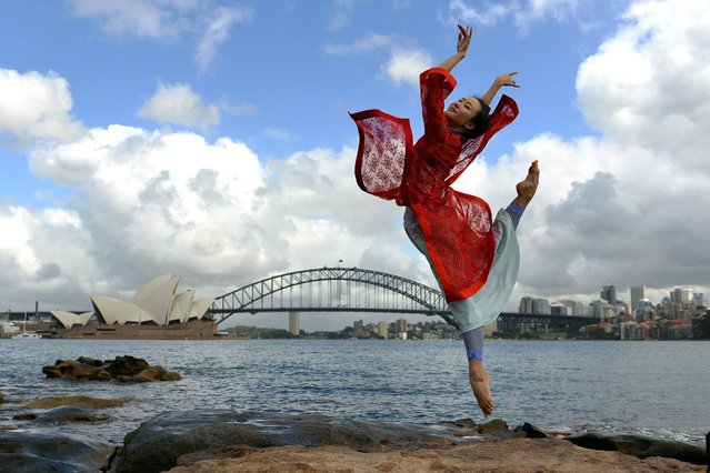 Performer Zhang Yashu from a Chinese ballet company perform during a photo shoot in front of the Australia's iconic landmarks Opera House (L) and Habour Bridge in Sydney on February 17, 2014. One of China's celebrated dance campanies is bringing one of the country's biggest ballet production to Australia for a series of performances in Sydney and Melbourne. (Photo by Saeed Khan/AFP Photo)
