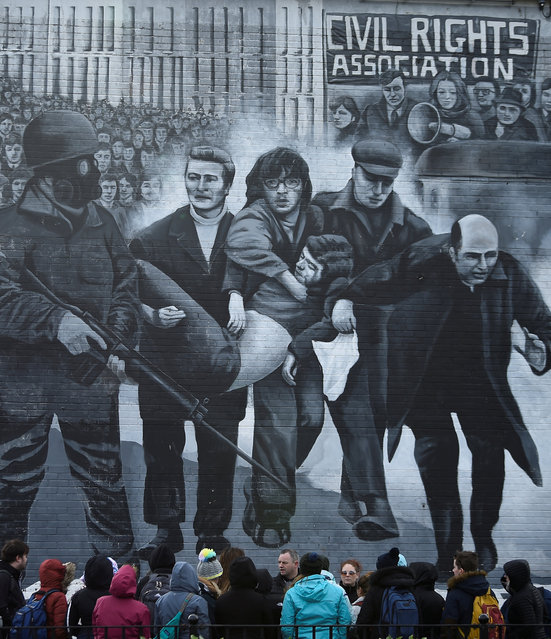 Tourists stand in front of a mural depicting the Bloody Sunday events, in Londonderry, Northern Ireland March 14, 2019. (Photo by Clodagh Kilcoyne/Reuters)