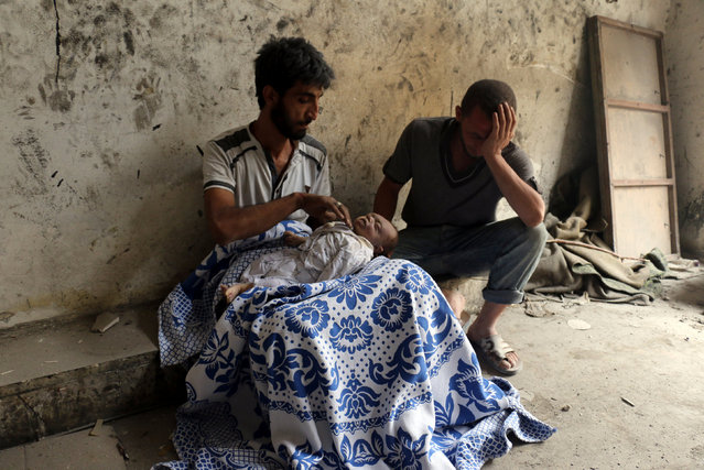 Syrians mourn over the body of a baby following bombardment on Aleppo's al-Marja neighborhood on 23 September 2016. Missiles rained down on rebel-held areas of Aleppo, causing widespread destruction that overwhelmed rescue teams, as the army prepared a ground offensive to retake the city. (Photo by Ameer Alhalbi/AFP Photo/Courtesy of World Press Photo Foundation)