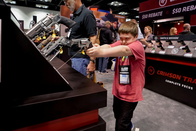 A young attendee handles a handgun during the annual National Rifle Association (NRA) annual meeting at the Indiana Convention center in Indianapolis, Indiana, U.S., April 26, 2019. (Photo by Bryan Woolston/Reuters)