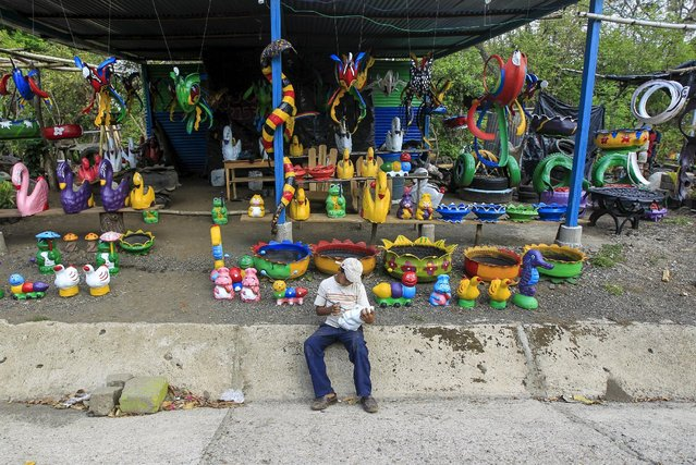 Carlos Salazar (10), paints a pig figurine made of concrete in a shop located on the Panamerican highway near Catarina town May 7, 2015. (Photo by Oswaldo Rivas/Reuters)