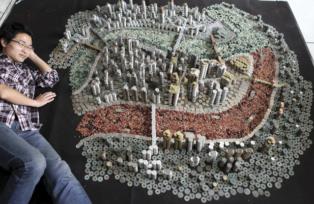 He Peiqi, lies as he poses for photographs next to a replica of Chongqing city that he made out of coins, in Chongqing municipality, China, May 10, 2015. He, in his 30s, collects and trades different types of coins for a living. (Photo by Reuters/Stringer)